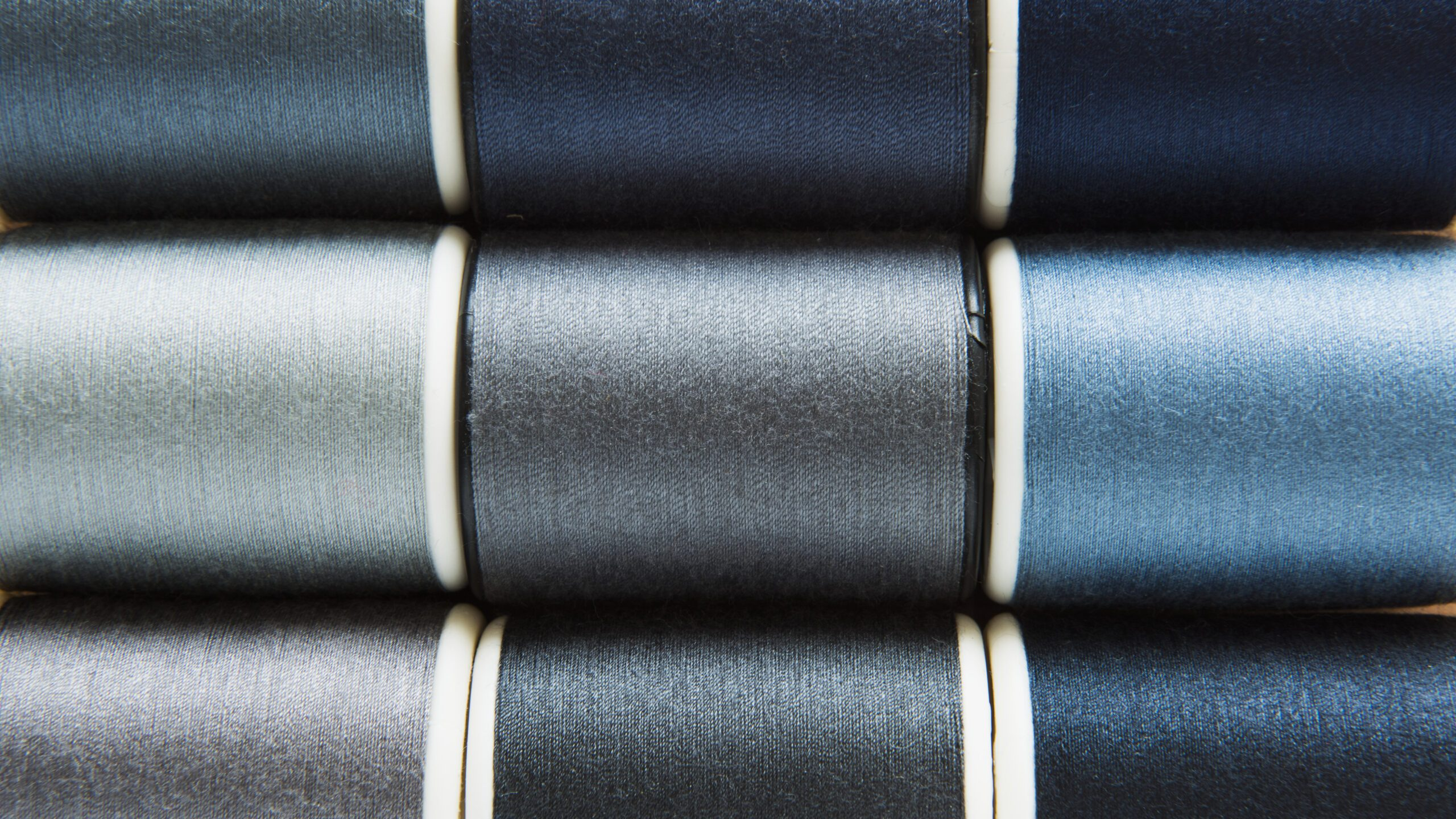 shades gray blue sewing threads background closeup